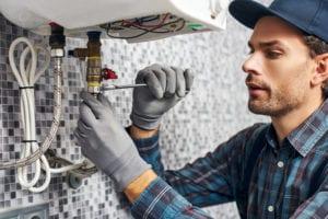 plumber working on a water heater repair in somerdale