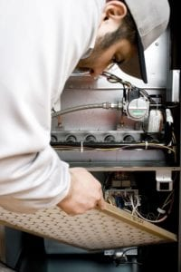 a technician repairs a furnace in cherry hill