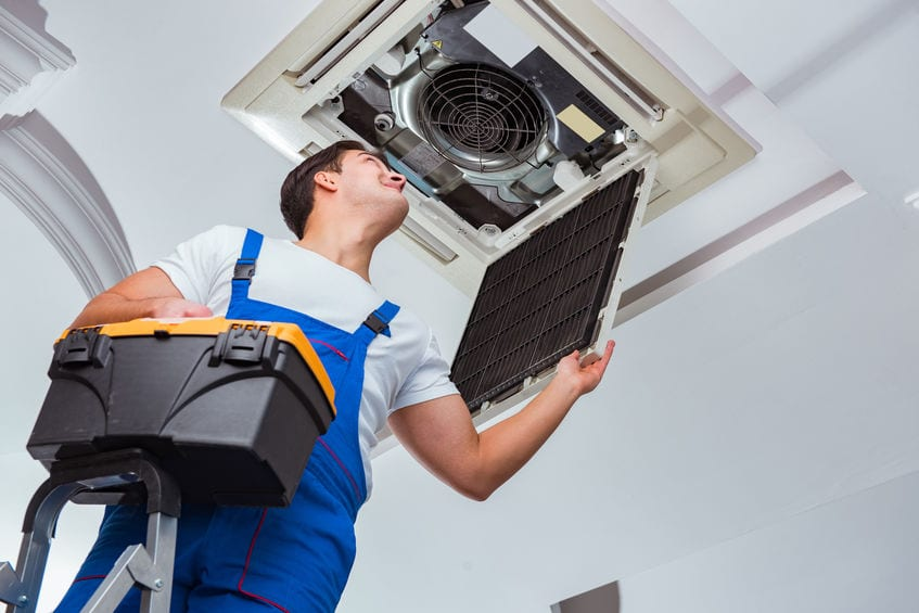 technician performing air conditioning maintenance in cherry hill nj