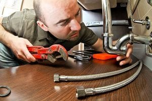 a man works with a wrench | burlington plumber