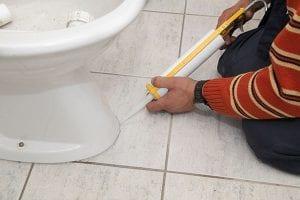 a person works with a caulking gun | burlington plumber